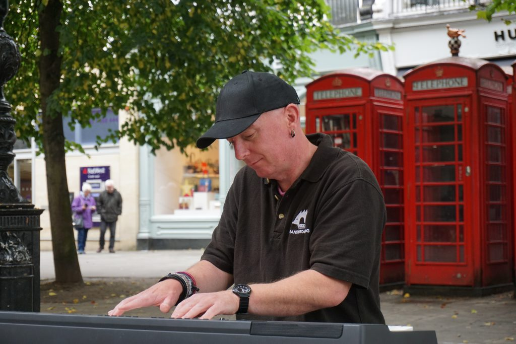 Busking live piano looking down next to red phone boxes